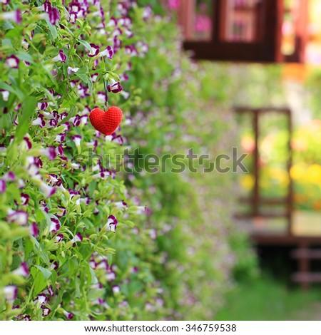 Handmade crochet heart on Flowers in the garden, valentines day concept - stock photo