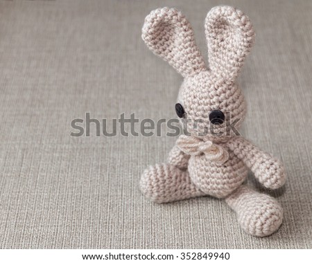 Handmade crochet rabbit toy on burlap rustic background. Amigurumi doll, space for text  - stock photo
