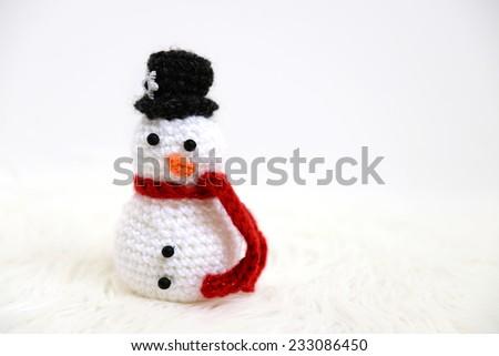 Handmade crochet snowman toy on white fur - stock photo