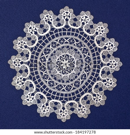 Handmade doily on blue background - stock photo