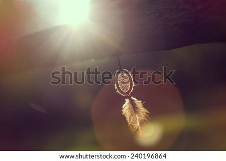 Handmade dream catcher hanging on a wooden fence in sunset of a beautiful sunny day - stock photo