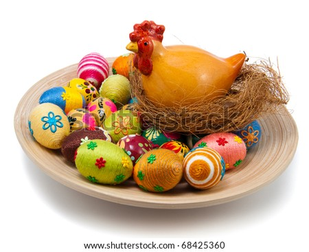 Handmade easter eggs on wooden plate. Small eggs are covered by cotton string in different colors. Additional decorative elements are glued to egg. Small ceramic hen in nest is placed.