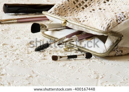 Handmade embroidery handbag with metal clasp with cosmetic brushes on the white stucco table is opened