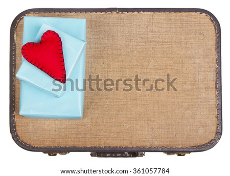 Handmade felt hearts with black stitching sitting on presents on top of an old vintage suitcase - stock photo