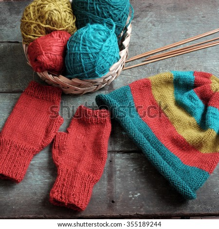 Handmade gift for winter, knitted gloves and knit hat for cold day, group of colorful yarn make warm, knit accessories is hobby activity of woman - stock photo