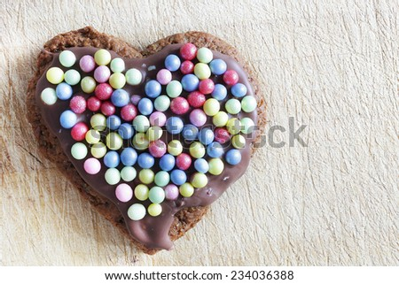 Handmade gingerbread heart decorated with colorful sugar pearls. Christmas, Valentines Day, love symbol. - stock photo