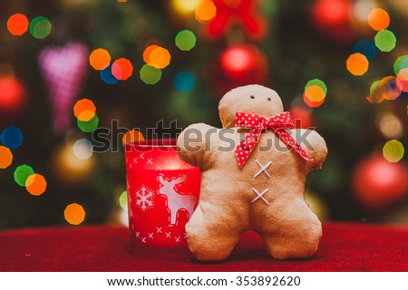 handmade gingerbread man and red candle with deer on the background of Christmas lights  - stock photo