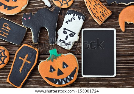 Handmade Halloween cookies on a wooden background and a blackboard - stock photo