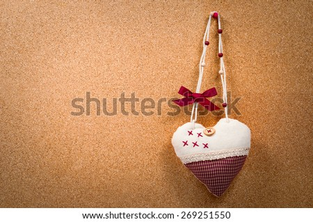 Handmade heart cloth hanging on the side of a cork board symbol romance valentines  - stock photo