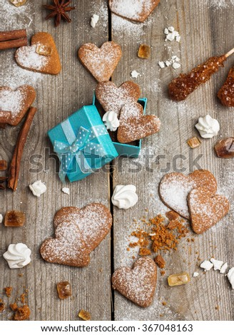 Handmade heart cookies for Valentines day in a gift box on a rustic wooden table. Selective focus, top view