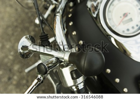 handmade horn on the bike handlebar and speedometer - stock photo