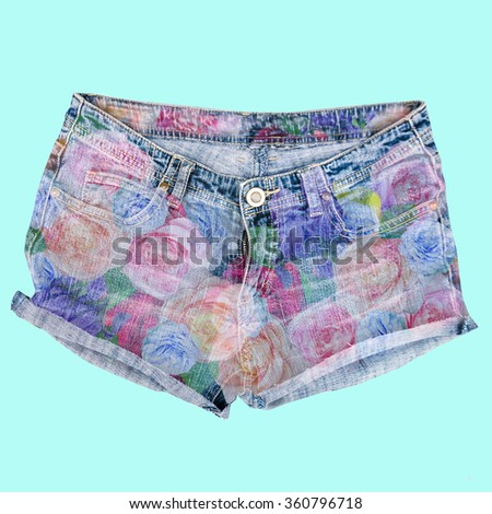 Handmade jeans shorts with floral print isolated on  blue background - stock photo