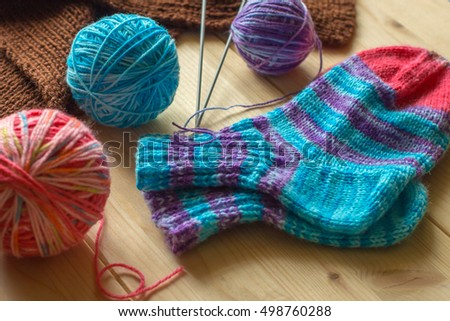 Handmade knitted baby multicolored socks and skeins of thread on light wooden boards