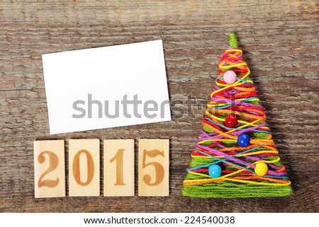 Handmade knitted Christmas tree with numbers 2015 on old wooden background - stock photo