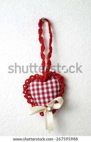 handmade knitted heart shape hanging on the white wall - stock photo
