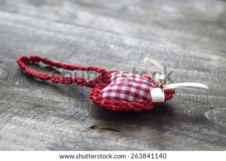 handmade knitted heart shape on wooden background - stock photo