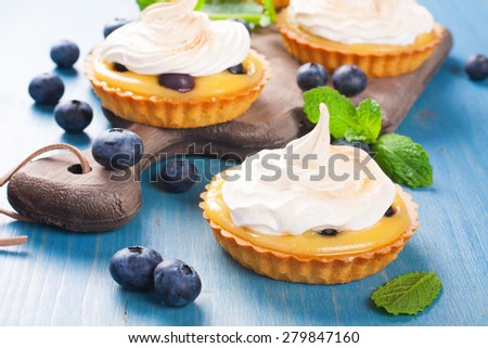 Handmade little tarts, cakes, tartlets with lime curd, meringue en berries on old rustik board on blue wooden background. Selective focus. - stock photo