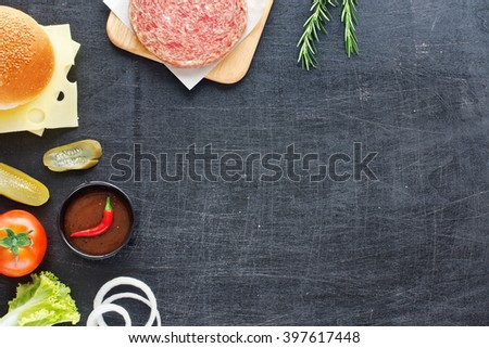 Handmade minced beef burger, bun, cheese, tomato, lettuce, onion, pickle, hot BBQ sauce. Black board background. Space for text. - stock photo
