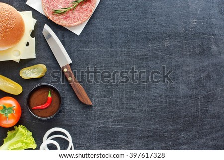 Handmade minced beef burger, bun, cheese, tomato, lettuce, onion, pickle, hot BBQ sauce, chili. Black board background. Space for text. - stock photo