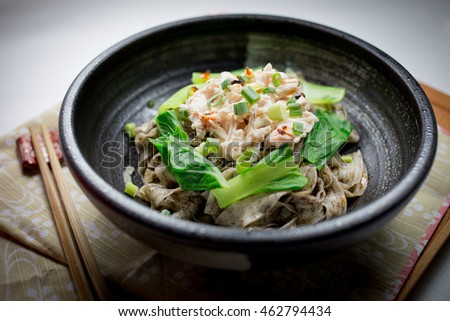 Handmade noodles with black sesame sauce and soy sauce. Boiled chicken, boiled vegetables, chopped green onion and spicy oil on top.