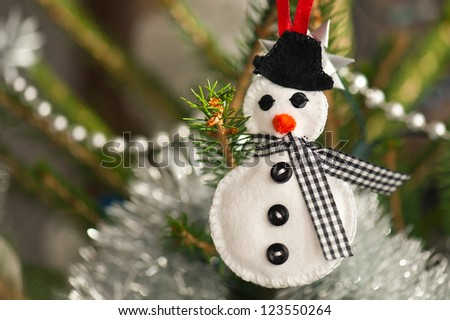 Handmade of felt snowman hanging on a Christmas tree - stock photo