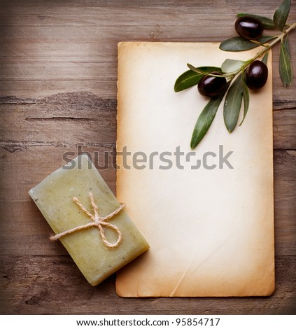 Handmade Olive Soap and Blank Paper with Olive Branch over Wooden Background - stock photo