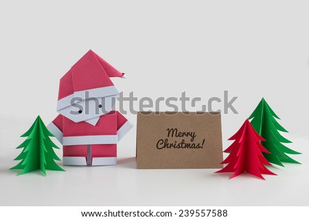 Handmade origami Santa Claus paper craft with christmas trees and a merry christmas card - stock photo