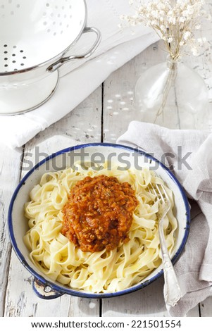 handmade pasta with ragout sauce on plate on vintage white table with colander and flowers - stock photo