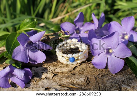 Handmade pearl ring with wood violet in spring on the nature background - stock photo