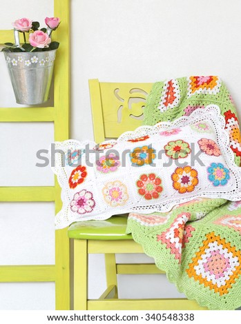Handmade pillow and blanket on the chair.Cozy home decorations