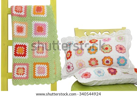 Handmade pillows on the chair and  blanket draped over a decorative ladder, isolated on white