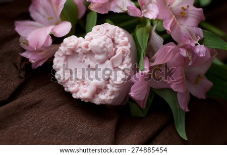 handmade pink soap in shape of cupid with flowers - stock photo