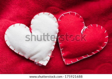 Handmade plush red hearts couple on soft blanket. Romantic love, Valentine's Day concepts. - stock photo