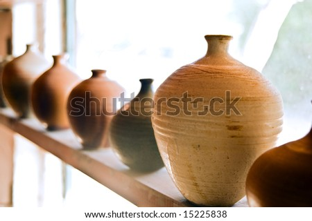 handmade pots/vases on a shelf at workshop - stock photo