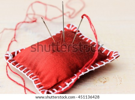 Handmade red silk needle cushion on white wooden background, Concept for homework or crafts theme