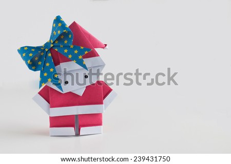 Handmade Santa Claus (girl) paper craft on white background with empty space on the right-hand side for writing your own message - stock photo
