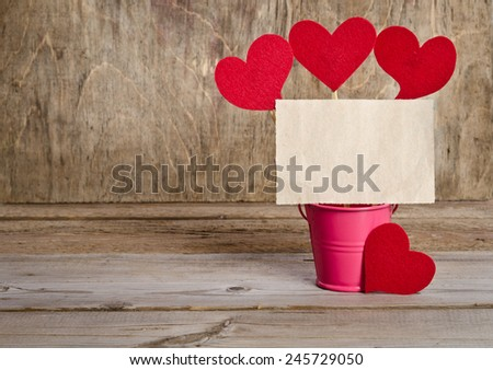 handmade skewers with cloth hearts and piece of old paper for guests for celebration of St. Valentine's Day on wooden background - stock photo
