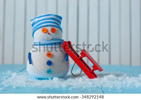 Handmade snowman in striped cap with red sled on snow In winter. Christmas postcard background, empty space for text. - stock photo