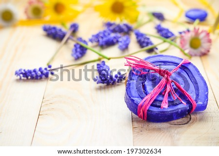Handmade soap and flowers on a wooden table - stock photo