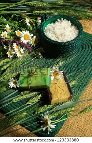 handmade soap with melissa, chamomile, poppy seeds on the background of wild flowers - stock photo