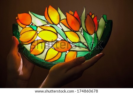 Handmade stained glass lamp with tulips flowers in woman's hands - stock photo