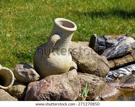 Handmade stone jar as a decoration item in a garden - stock photo