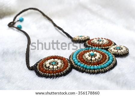 Handmade stone necklaces Turquoise. On white wool - stock photo