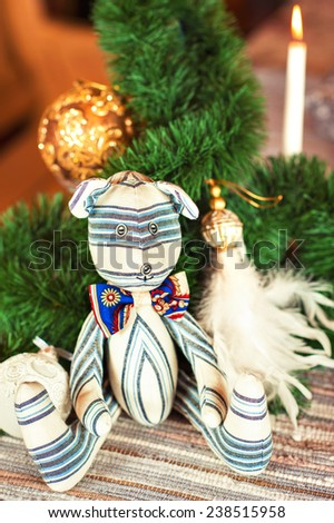 Handmade striped tilda bear toy on christmas background. Celebration gift. Indoors still-life. - stock photo