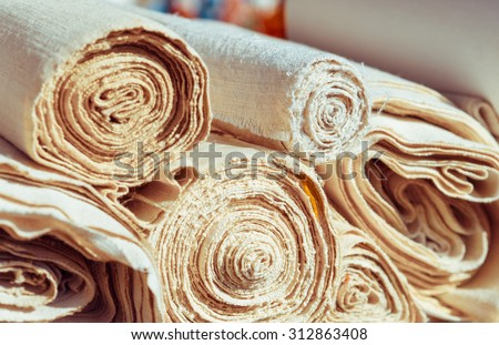 Handmade textile in retro style - natural  fabric of flax and cotton. Canvas and burlap in rolls closeup - homespun fabric of handwork. - stock photo