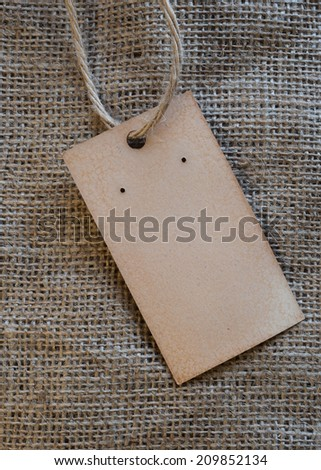 handmade vintage tag label on burlap background - stock photo