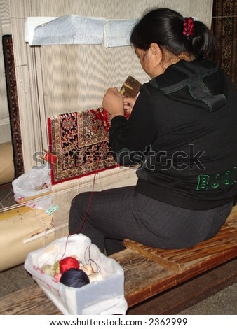 Handmade weaving of a silk rug on an ancient loom in a Factory, China