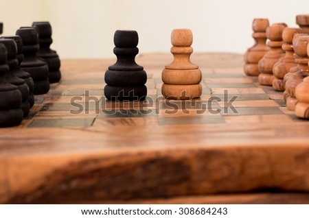 handmade wooden chess board, two pawns face off