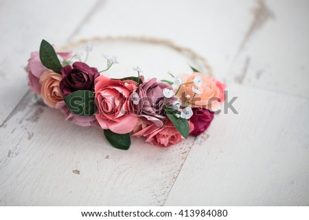 Handmade wraith or tiara made of pink and red rose flowers lying on bright white wooden background. Shallow depth of field, macro close up, copy space  - stock photo