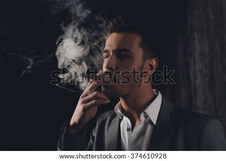 Handome confident man in suit on the grey background smoking a cigar - stock photo